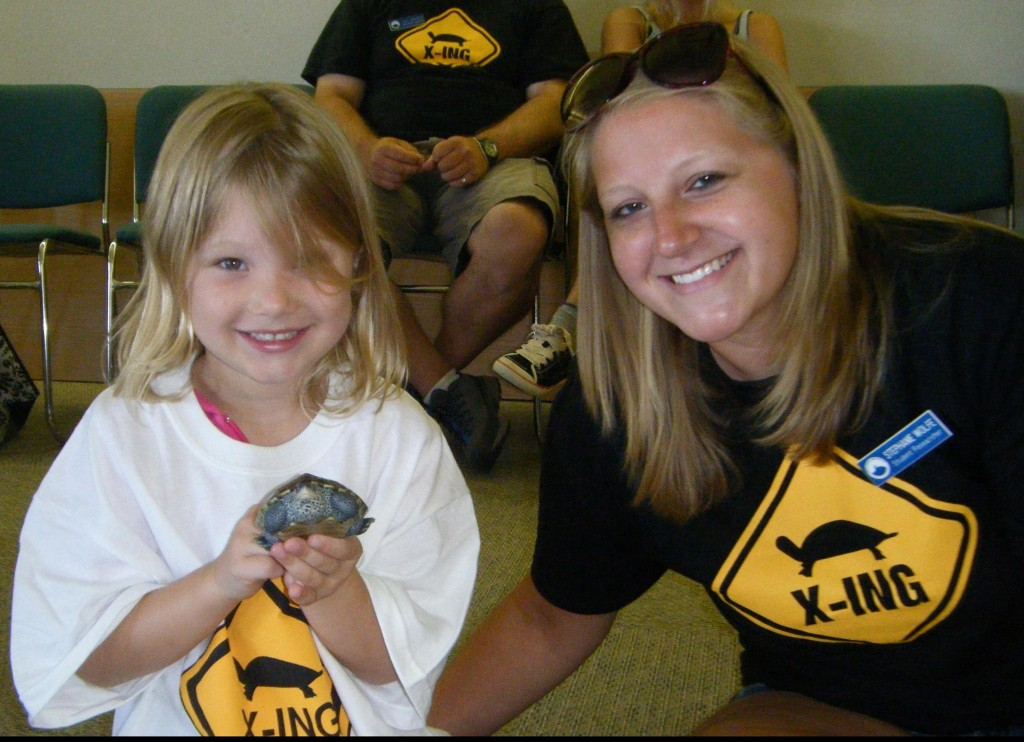 Student researcher shows local kindergartener a terrapin head-starter.  Later that day, the kindergarteners released twenty one head-starters back into the wild.